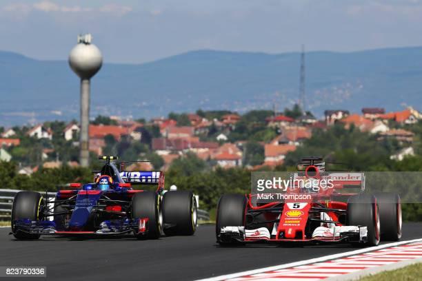 Sebastian Vettel of Germany driving the Scuderia Ferrari SF70H and Carlos Sainz of Spain driving the Scuderia Toro Rosso STR12 on track during...