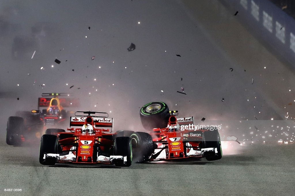 Sebastian Vettel of Germany driving the (5) Scuderia Ferrari SF70H and Kimi Raikkonen of Finland driving the (7) Scuderia Ferrari SF70H collide at the start during the Formula One Grand Prix of Singapore at Marina Bay Street Circuit on September 17, 2017 in Singapore.