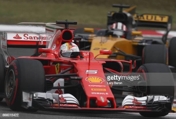 Sebastian Vettel of Germany driving the Scuderia Ferrari SF70H leads Nico Hulkenberg of Germany driving the Renault Sport Formula One Team Renault...