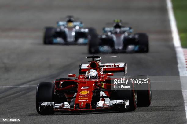 Sebastian Vettel of Germany driving the Scuderia Ferrari SF70H leads Valtteri Bottas driving the Mercedes AMG Petronas F1 Team Mercedes F1 WO8 and...