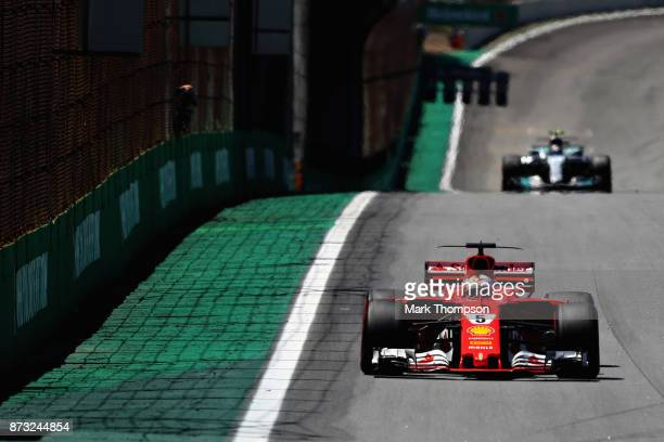 Sebastian Vettel of Germany driving the Scuderia Ferrari SF70H leads Valtteri Bottas driving the Mercedes AMG Petronas F1 Team Mercedes F1 WO8 on...