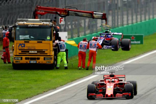 Sebastian Vettel of Germany driving the Scuderia Ferrari SF71H as the car of Brendon Hartley of New Zealand and Scuderia Toro Rosso is removed from...