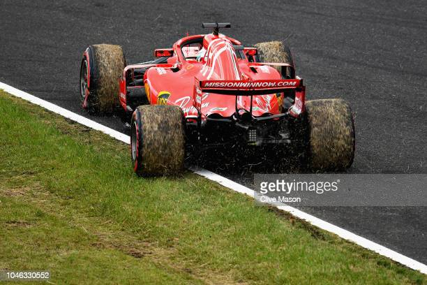 Sebastian Vettel of Germany driving the Scuderia Ferrari SF71H kicks up grass after spinning during qualifying for the Formula One Grand Prix of...