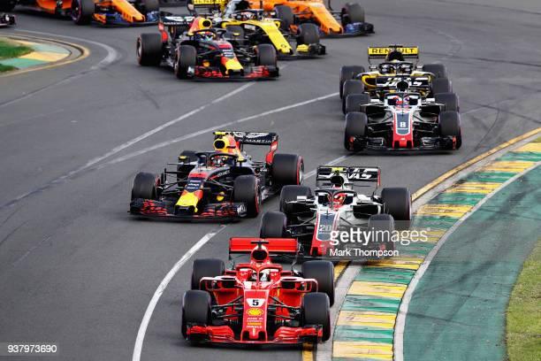 Sebastian Vettel of Germany driving the Scuderia Ferrari SF71H leads Kevin Magnussen of Denmark driving the Haas F1 Team VF18 Ferrari Max Verstappen...