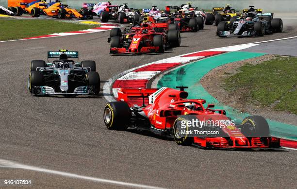 Sebastian Vettel of Germany driving the Scuderia Ferrari SF71H leads Valtteri Bottas driving the Mercedes AMG Petronas F1 Team Mercedes WO9 and the...