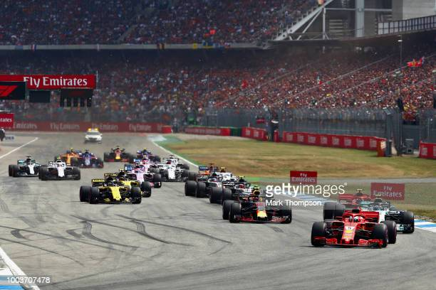 Sebastian Vettel of Germany driving the Scuderia Ferrari SF71H leadss the field at the start during the Formula One Grand Prix of Germany at...