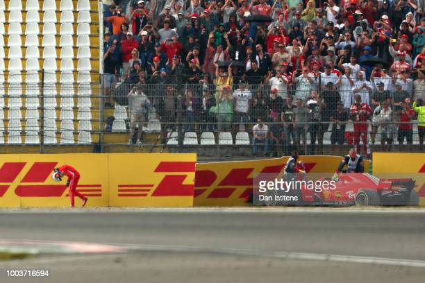 Sebastian Vettel of Germany driving the Scuderia Ferrari SF71H walks from his car after crashing during the Formula One Grand Prix of Germany at...