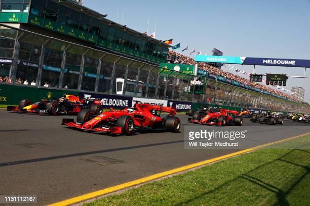 Sebastian Vettel of Germany driving the Scuderia Ferrari SF90 battles with Max Verstappen of the Netherlands driving the Aston Martin Red Bull Racing...