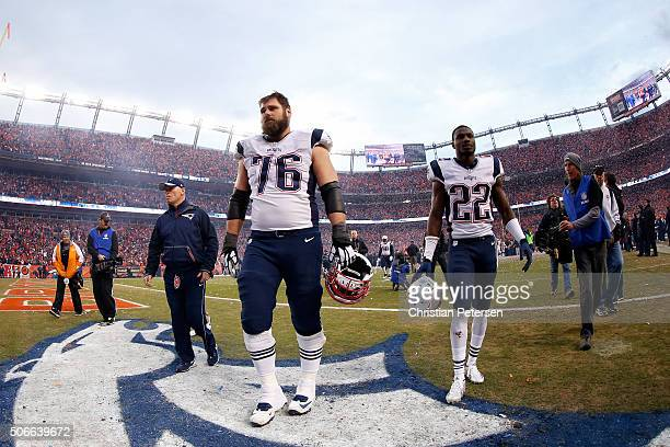 Sebastian Vollmer and Justin Coleman of the New England Patriots walk off the field with teammates after being defeated by the Denver Broncos in the...