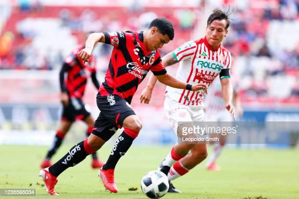 Sebastian Yanez of Club Tijuana competes for the ball with Fernando Gonzalez of Necaxa during the 11th round match between Necaxa and Club Tijuana as...