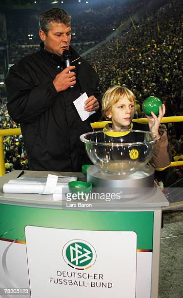 Sebastian young fan of Dortmund draws the semifinals for the DFB JuniorenCup next to Norbert Dickel of Dortmund during the Bundesliga match between...