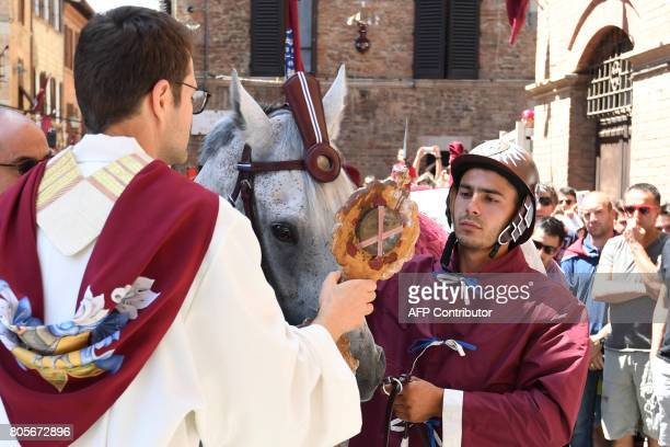 Sebastiano Murtas known as Grandine and his horse Querida de Marchesana receives a blessing before the 'Contrada della Torre' on July 2 2017 in Siena...