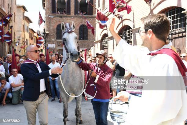 Sebastiano Murtas known as Grandine stands next to his horse Querida de Marchesana as it receives the blessing before the 'Contrada della Torre' on...