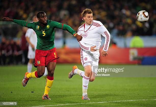Sebastien Bassong of Cameroon challenges Nicklas Bendtner of Denmark during the 2010 FIFA World Cup South Africa Group E match between Cameroon and...