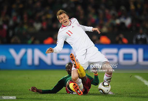 Sebastien Bassong of Cameroon tackles Nicklas Bendtner of Denmark during the 2010 FIFA World Cup South Africa Group E match between Cameroon and...