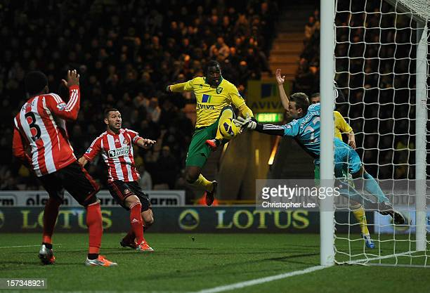 Sebastien Bassong of Norwich City scores the opening goal past Simon Mignolet of Sunderland during the Barclays Premier League match between Norwich...