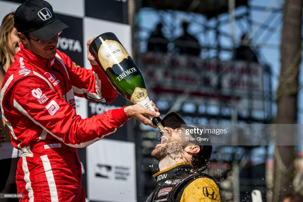 Sebastien Bourdais L of France pours champagne on race winner James Hinchcliffe of Canada in victory lane after the Grand Prix at Long Beach IndyCar race on April 9, 2017 in Long Beach California.