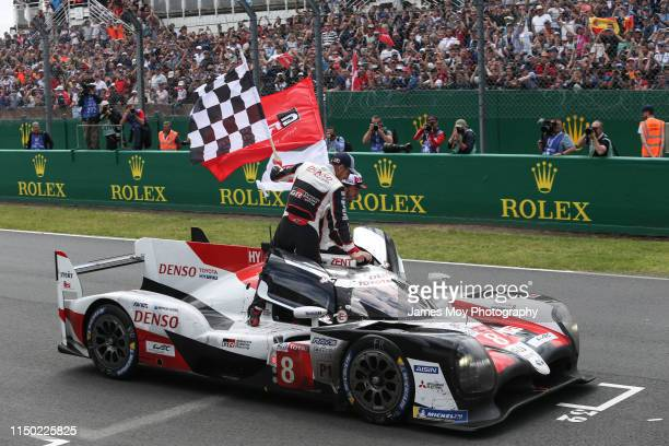 Sebastien Buemi of Switzerland and Toyota Gazoo Racing and Fernando Alonso of Spain and Toyota Gazoo Racing celebrate as Kazuki Nakajima of Japan and...