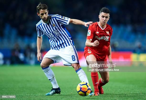Sebastien Corchia of Sevilla FC being followed by Adnan Januzaj of Real Sociedad during the La Liga match between Real Sociedad and Sevilla at...
