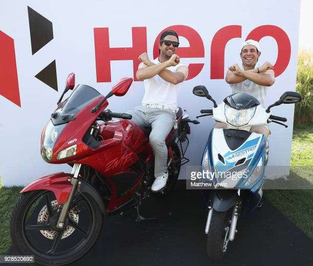 Sebastien Gros and Adrien Saddier of France sit on motorbikes as they wait to tee off on the 16th hole during a practice round ahead of the Hero...