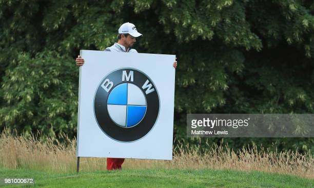 Sebastien Gros of France removes a sponsor board on the 12th hole during day two of the BMW International Open at Golf Club Gut Larchenhof on June 22...