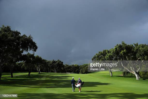 Sebastien Gros of France walks down the 10th fairway to get in position to restart play as a storm passes during day one of the Andalucia Valderrama...