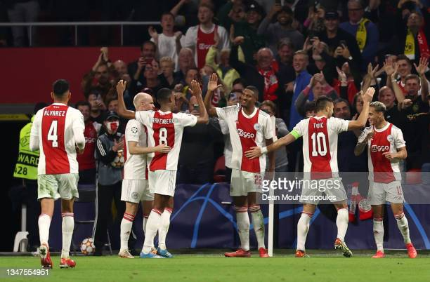 Sebastien Haller of Ajax celebrates after scoring their side's fourth goal with team mates during the UEFA Champions League group C match between AFC...