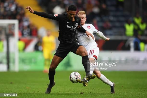 Sebastien Haller of Eintracht Frankfurt battles for the ball with Sebastian Kerk of Nurnberg during the Bundesliga match between Eintracht Frankfurt...