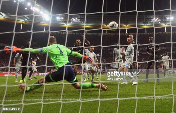 Sebastien Haller of Eintracht Frankfurt scores his team's third goal past Ralf Faehrmann of FC Schalke 04 during the Bundesliga match between...