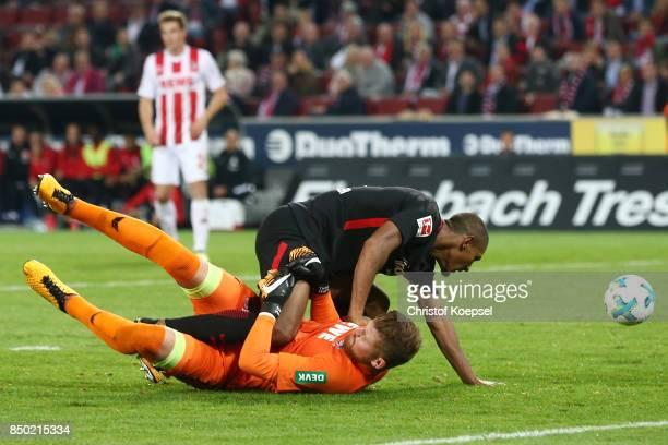 Sebastien Haller of Frankfurt falls over goalkeeper Timo Horn of Koeln during the Bundesliga match between 1. FC Koeln and Eintracht Frankfurt at...