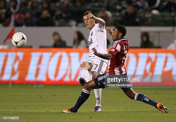 Sebastien Le Toux of the Vancouver Whitecaps crosses against James Riley of Chivas USA in the first half during the MLS match at The Home Depot...