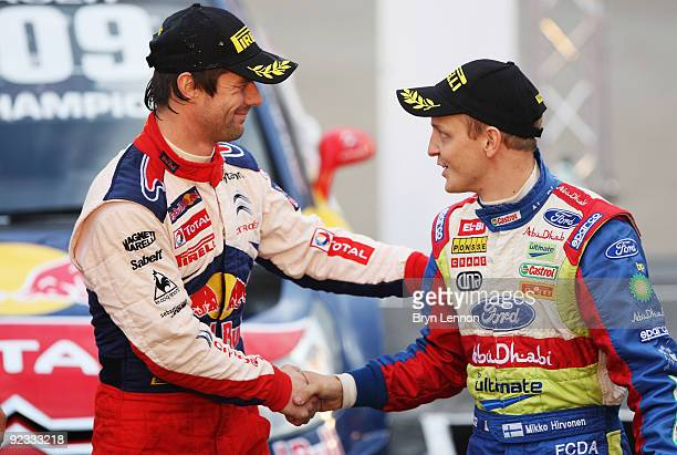 Sebastien Loeb of France and Citroen shakes hands with title rival Mikko Hirvonen of Finland and BP Ford Abu Dhabi World Rally Team after winning the...