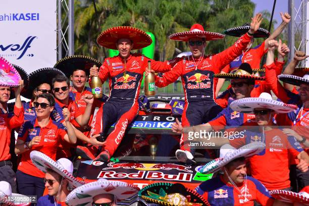 Sebastien Ogier of France and Julien Ingrassia of France celebrate with teammates in their Citroen Total WRT after their victory during day three of...