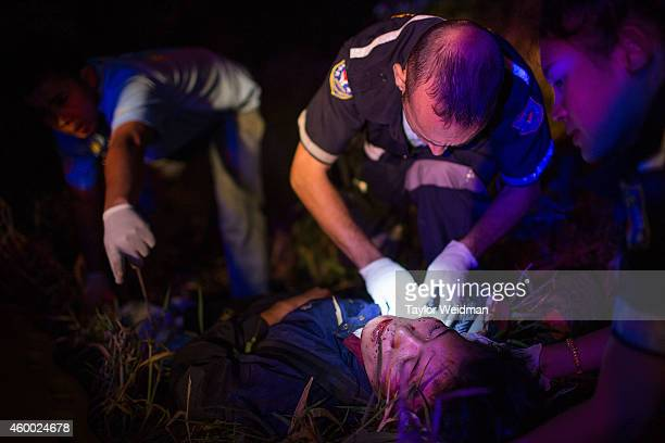Sebastien Perret the founder of Vientiane Rescue treats a severely injured motorbike accident victim on the side of the road on December 6 2014 in...