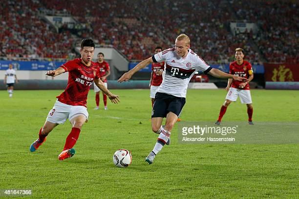 Sebastin Rode of Muenchen battles for the ball with Fang Mei of Guangzhou during the international friendly match between FC Guangzhou Evergrande...