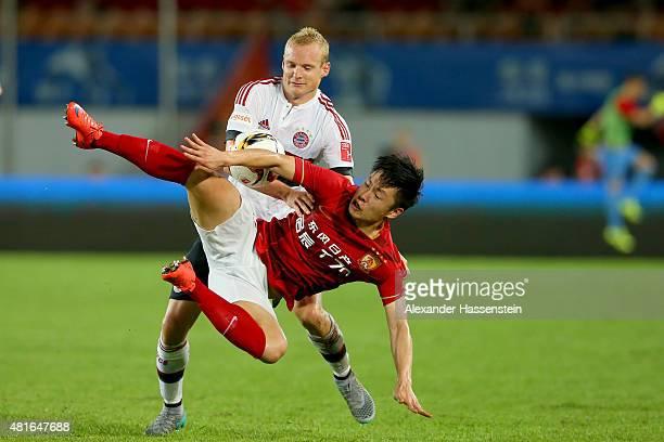 Sebastin Rode of Muenchen battles for the ball with Long Zheng of Guangzhou during the international friendly match between FC Guangzhou Evergrande...
