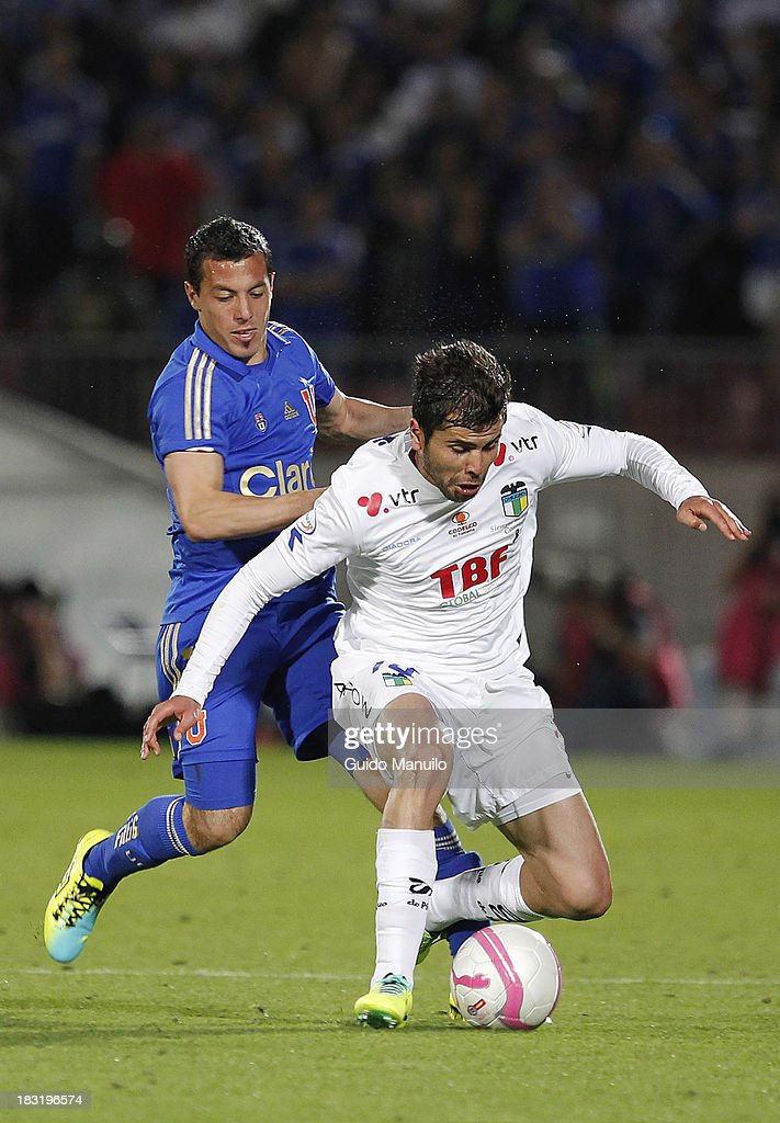 Sebastián Ubilla of U de Chile fights for the ball with Fernando Gutierrez during a match between O'Higgins and U de Chile as part of the Torneo Apertura at National Stadium, on October 05, 2013 in Santiago, Chile.