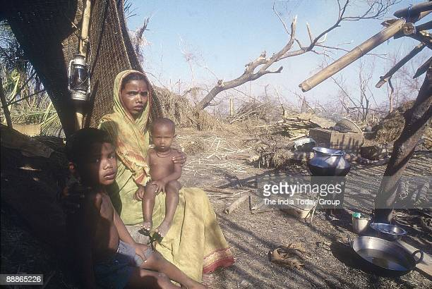 Sebati Senapati Cyclone Victims sitting in her destroyed house with her Children after the Cyclone In Orissa