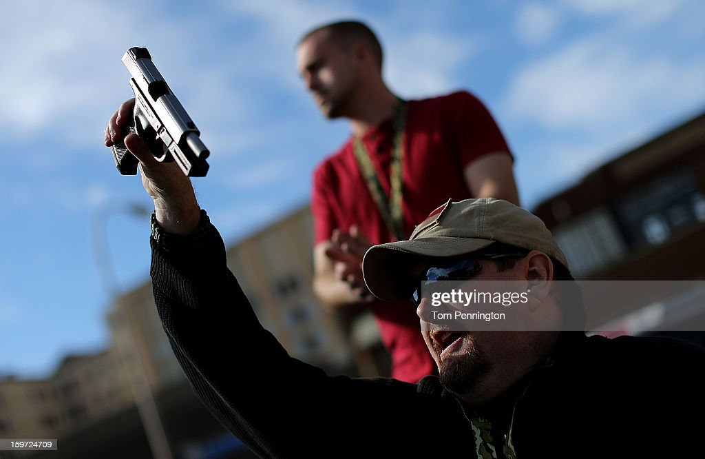 Second Amendment supporter and gun enthusiast Derek Ringley displays an unloaded pistol that was being sold in an impromptu auction across the street from a gun buy back program at the First Presbyterian Church of Dallas on January 19, 2013 in Dallas, Texas. U.S. President Barack Obama recently unveiled a package of gun control proposals that include universal background checks and bans on assault weapons and high-capacity magazines.