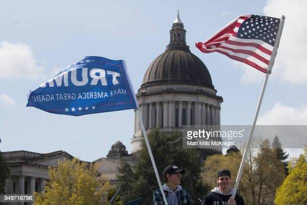 Second amendment supporters protest while holding a President Trump and American flag in front of the Washington State Capitol during March For Our...