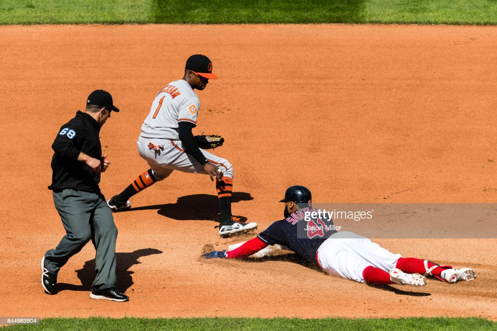 Second base umpire Chris Guccione #68 watches as shortstop Tim Beckham #1 of the Baltimore Orioles tries to tag Carlos Santana #41 of the Cleveland Indians as he reaches second on a hit during the fourth inning at Progressive Field on September 9, 2017 in Cleveland, Ohio.