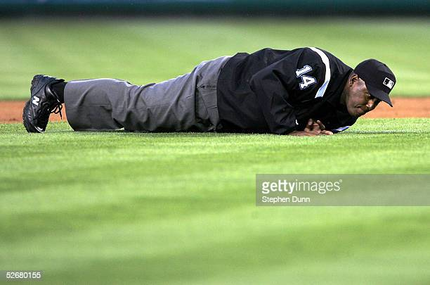 Second base umpire Chuck Meriwether lies on the grass after being hit by a ground ball in the game between the Los Angeles Angels of Anaheim and the...