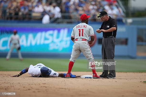 Second base umpire Dale Scott calls Yasiel Puig of the Los Angeles Dodgers safe during the game against the Philadelphia Phillies on Sunday June 30...
