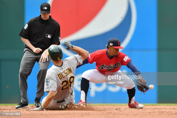 Second base umpire Nic Lentz watches as Matt Olson of the Oakland Athletics slides into second for a double as shortstop Francisco Lindor of the...