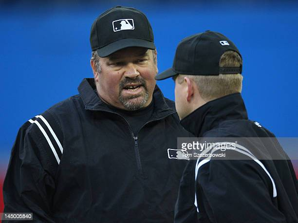 Second base umpire Wally Bell talks to first base umpire Mike Muchlinski during MLB game action between the New York Mets and the Toronto Blue Jays...