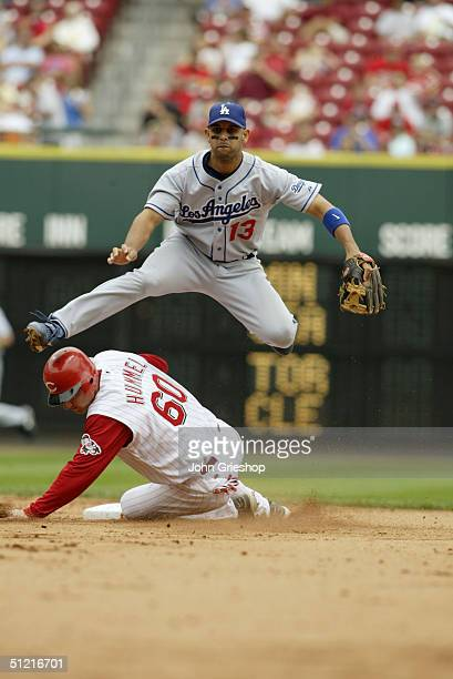 Second baseman Alex Cora of the Los Angeles Dodgers attempts the double play as infielder Tim Hummel of the Cincinnati Reds slides into second base...