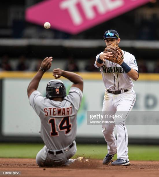 Second baseman Austin Nola of the Seattle Mariners turns a double play after forcing out Christin Stewart of the Detroit Tigers at second base on a...