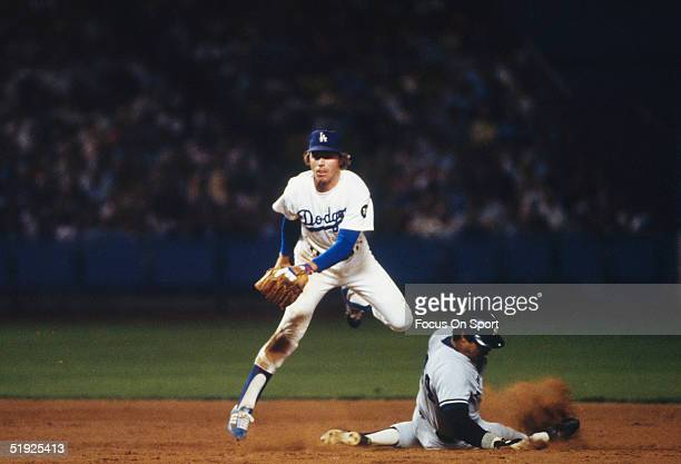 Second baseman Bill Russell of the Los Angeles Dodgers jumps to avoid Reggie Jackson of the New York Yankees who is sliding into second base during...