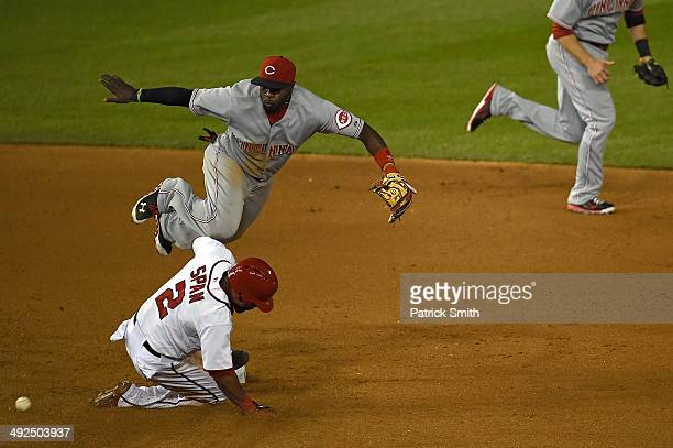 Second baseman Brandon Phillips of the Cincinnati Reds falls over Denard Span of the Washington Nationals as he steals second in the sixth inning at...