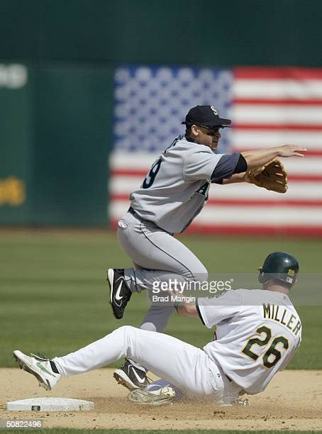 Second baseman Bret Boone of the Seattle Mariners attempts the double play as catcher Damian Miller of the Oakland Athletics slides into second base...